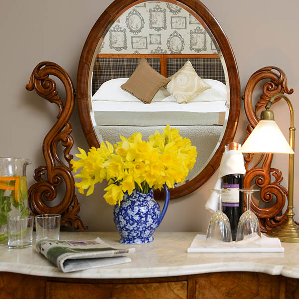 The Sea-View Junior Suite at Greenmount House B&B luxury accommodation in Dingle, Ireland, seen in the mirror with daffodils on the dressing table