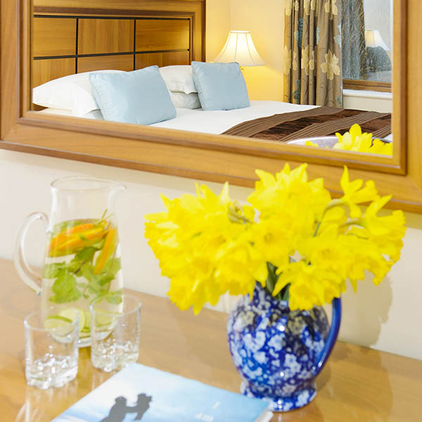 The Garden View Superior Room at Greenmount House B&B luxury accommodation in Dingle, Ireland, seen in the mirror with daffodils on the dressing table