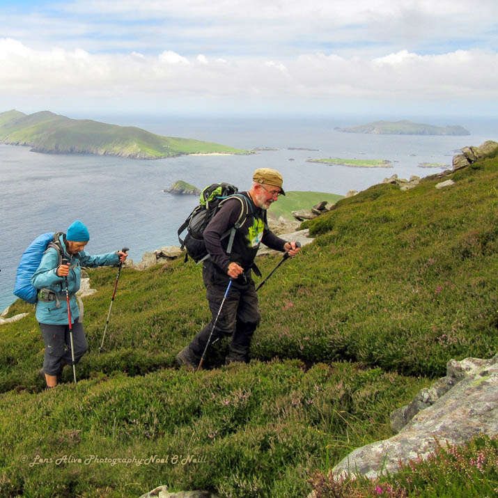 Two people hiking Mount Eagle, with a view of the Blasket Islands off the Dingle Peninsula