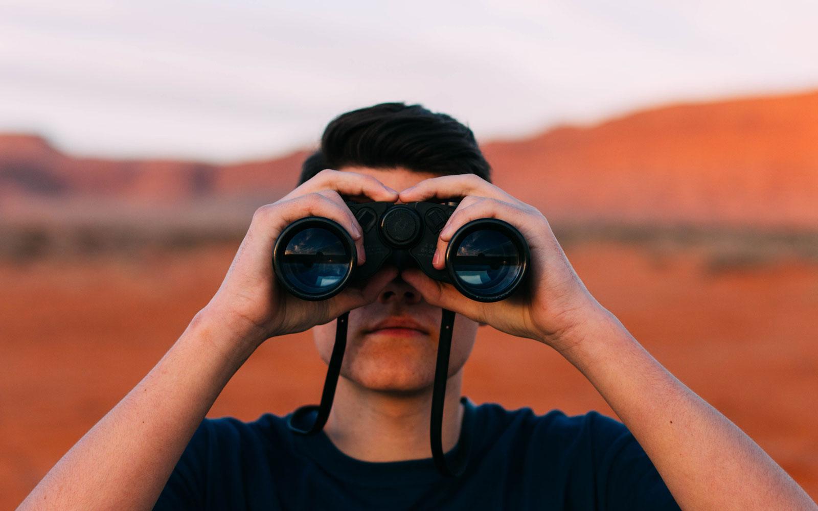 Man looking at the binoculars