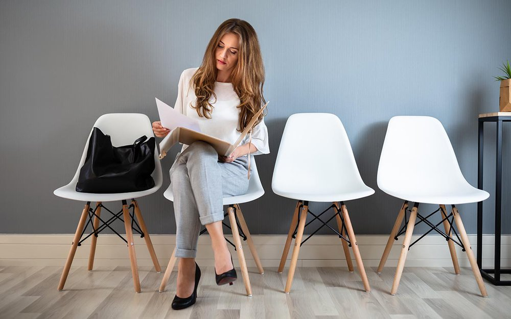 Young Business woman Holding Folder While Sitting On Chair Waiting For Job Interview