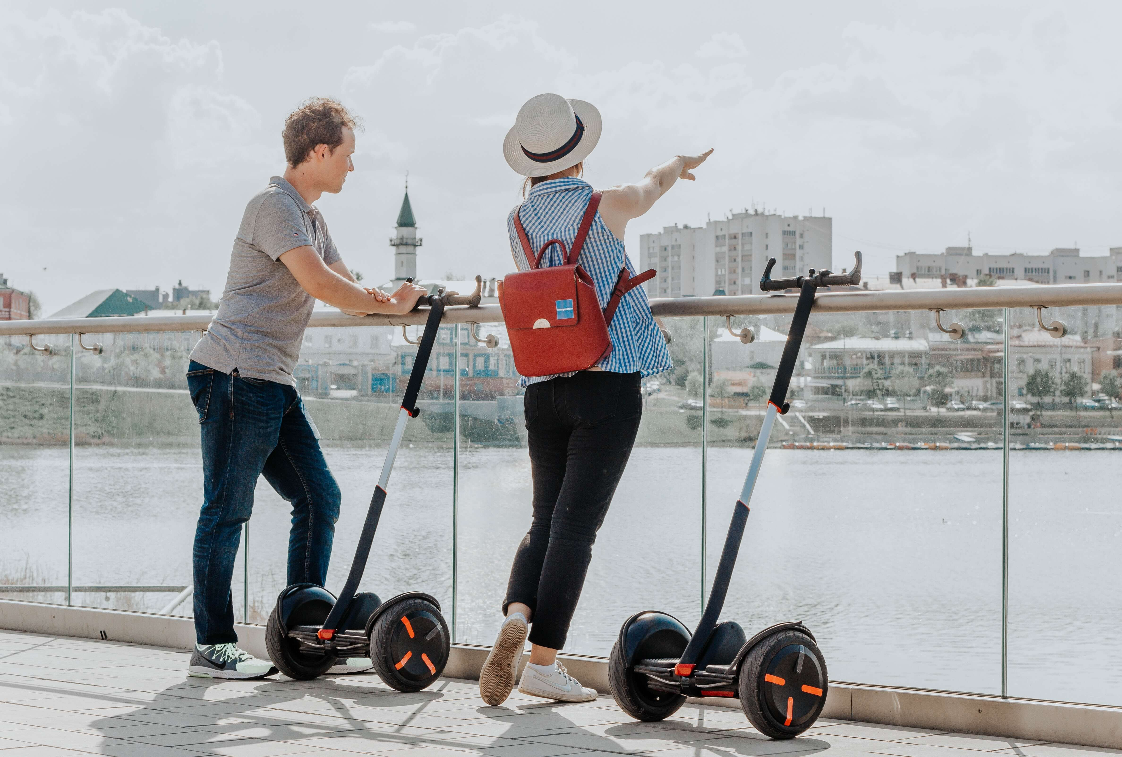 a man and a woman riding a segway on the river bank