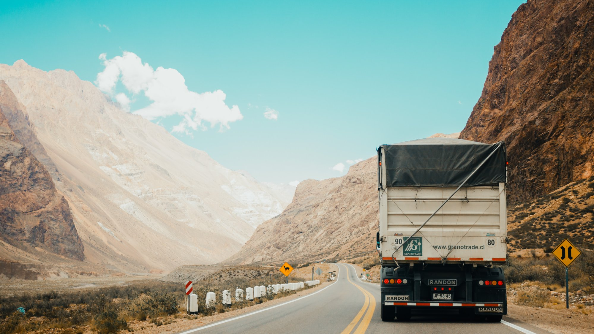 truck driving next to two mountains