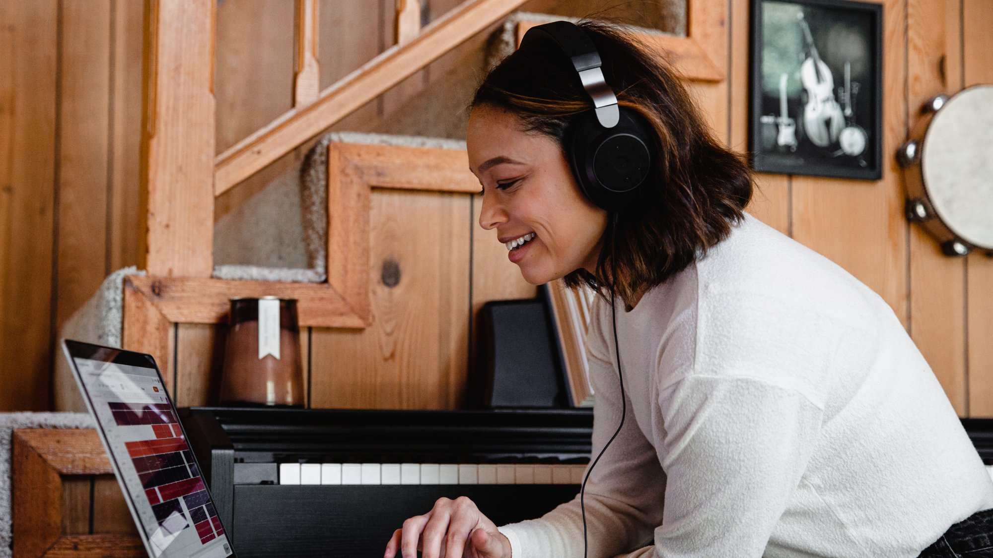woman looking down at a laptop with headphones on