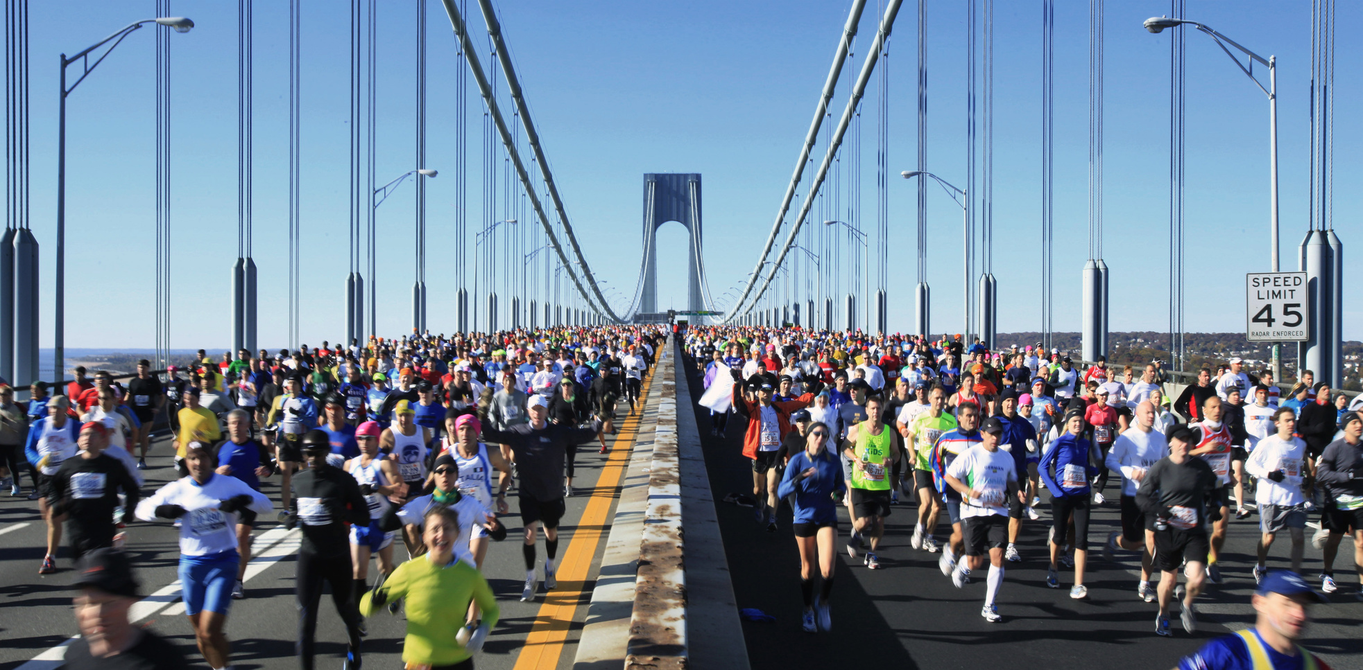 marathon racers running across a bridge