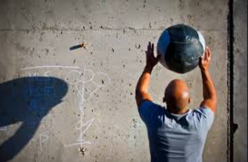 man throwing weighted ball against wall
