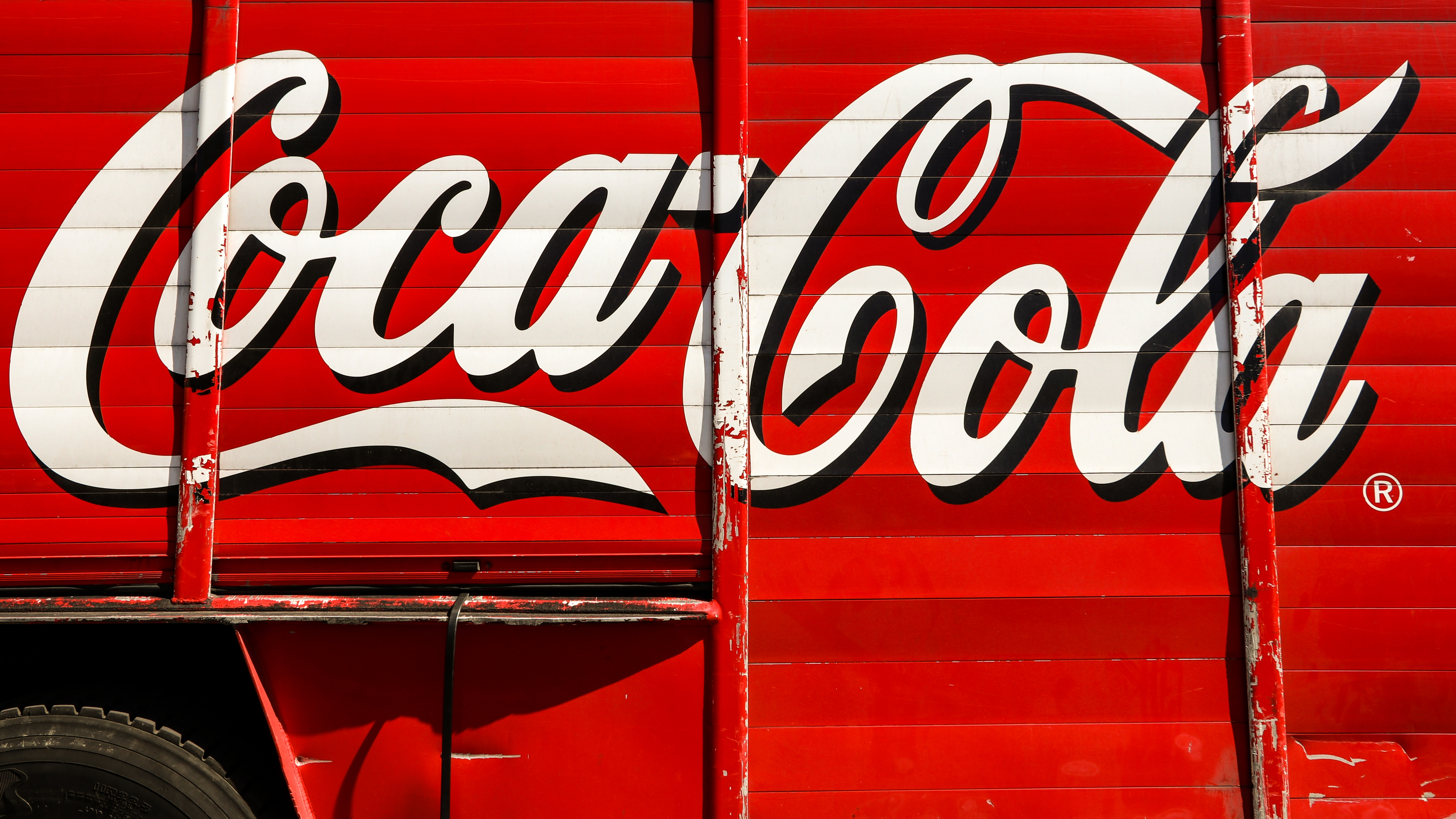 """<img alt=""""Coca-cola logo on the side of a red truck"""">"""