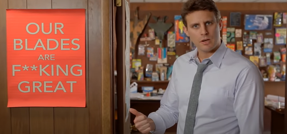 Still from a Dollar Shave Club advert with the owner in a shirt and tie coming out of his office and pointing at a poster that says 'our blades are f**king great'