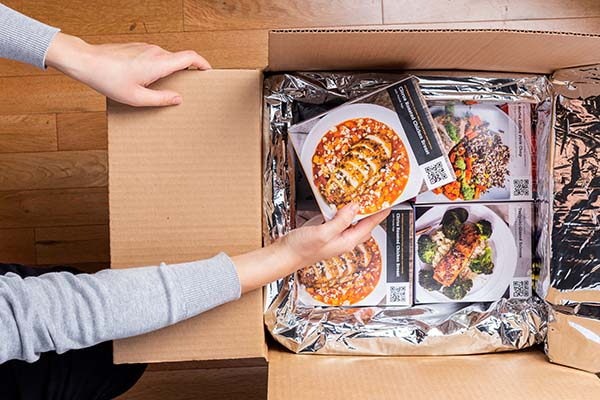 Hands removing packaged Tovala Meals from a delivery box.