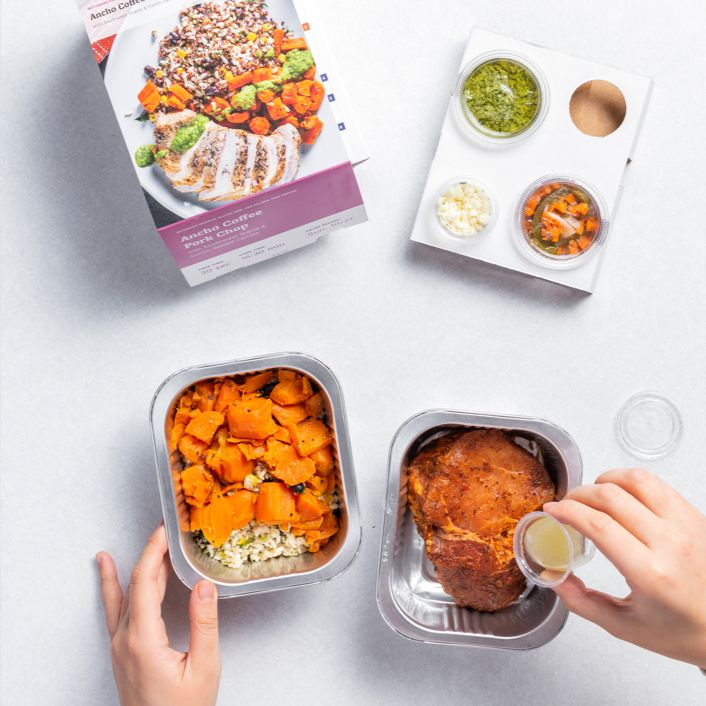 Overhead shot of Tovala Meals with hand pouring sauce into tray.