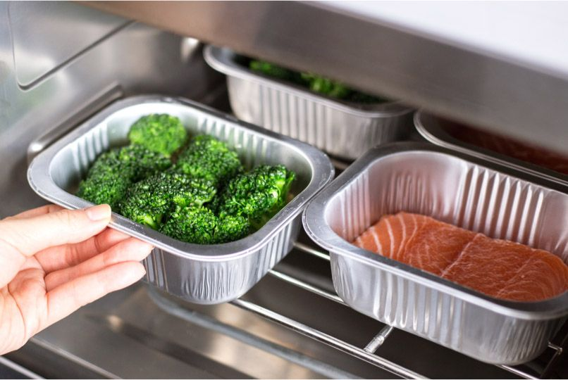 Tray of broccoli next to salmon in Tovala Steam Oven.