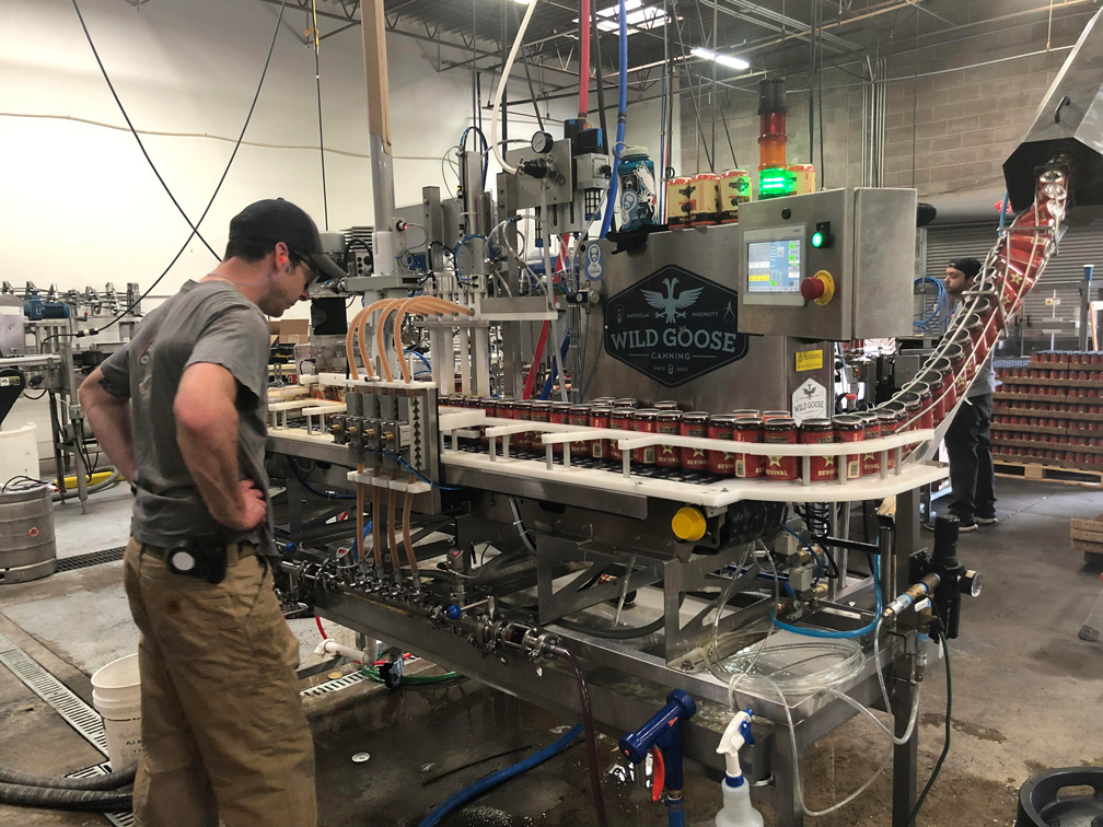 A photo of a Marshall Brewing Company employee running the canning line