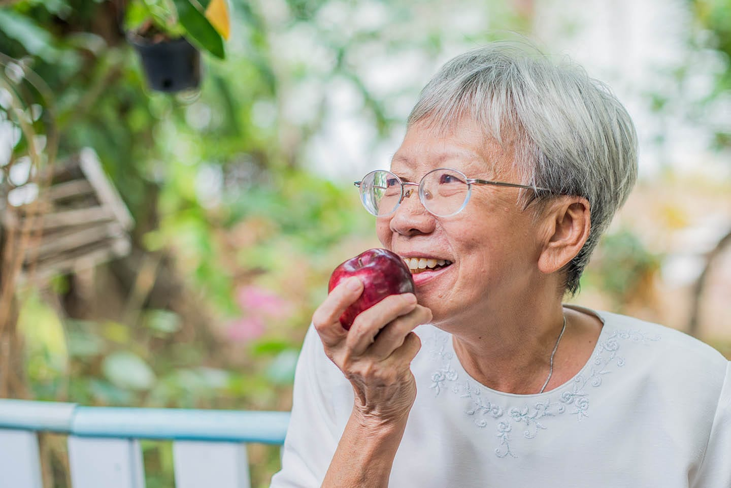 Older woman biting into a red apple
