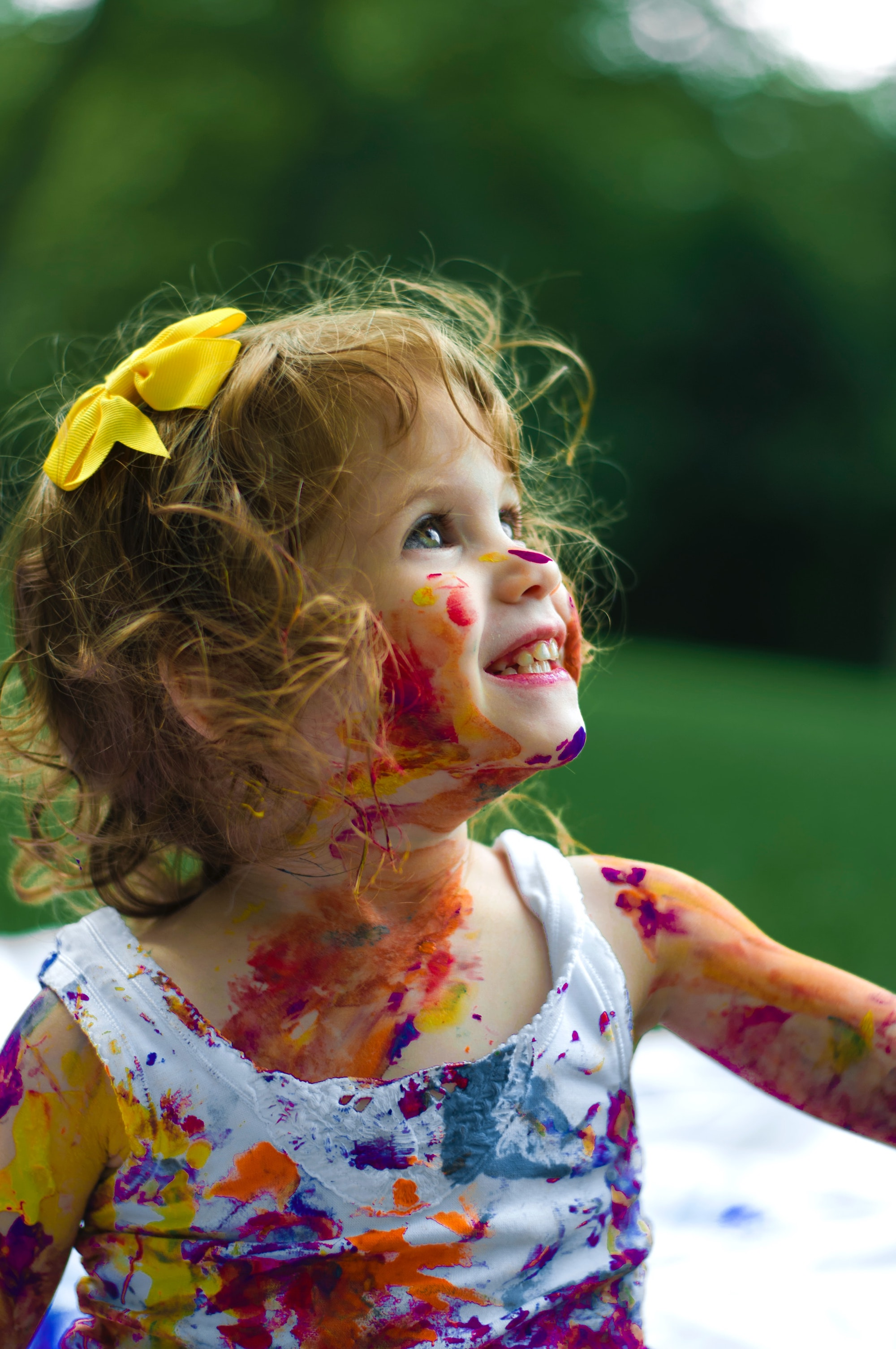 a kid smiling covered in paint