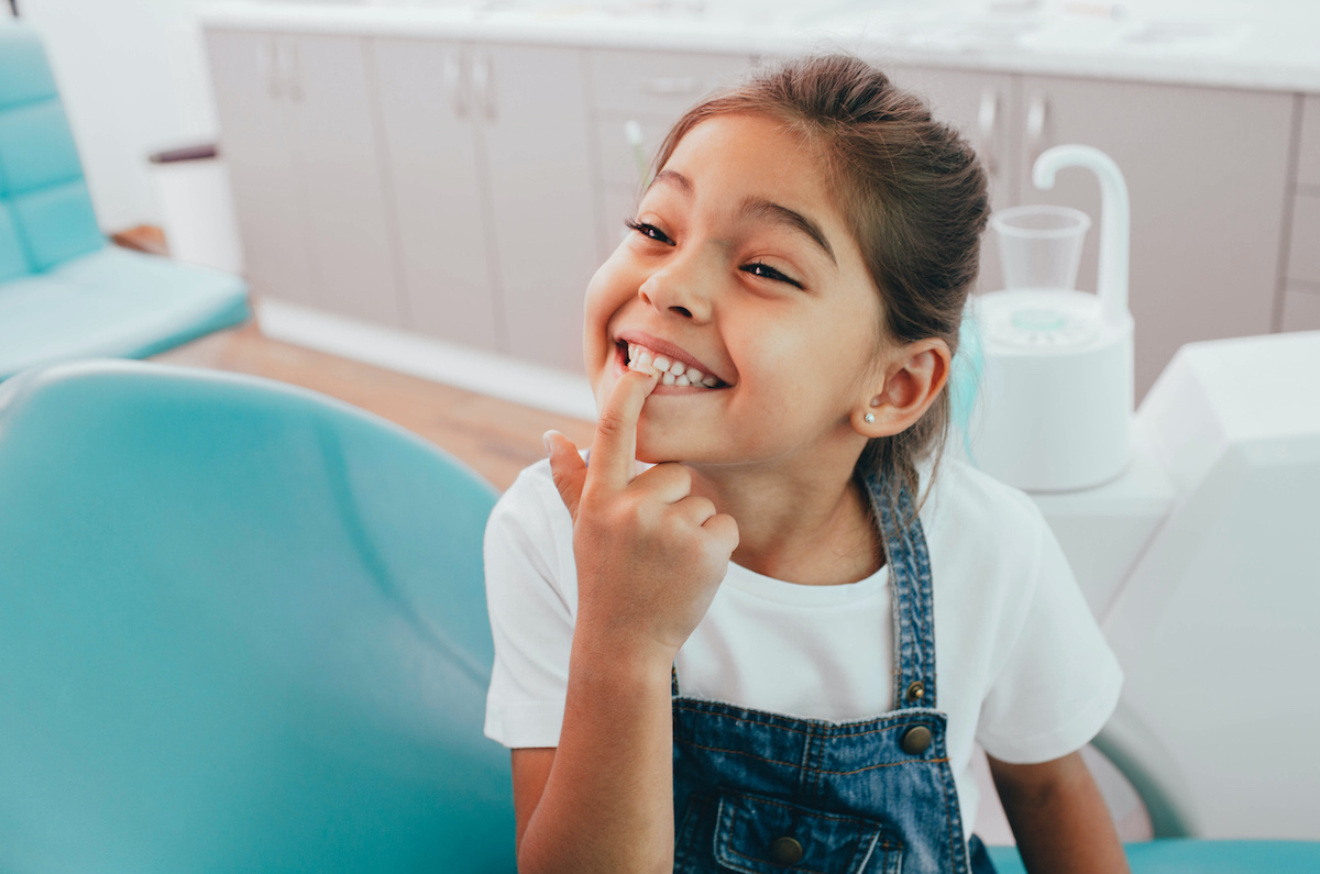 Child smiling while holding her extracted wisdom tooth