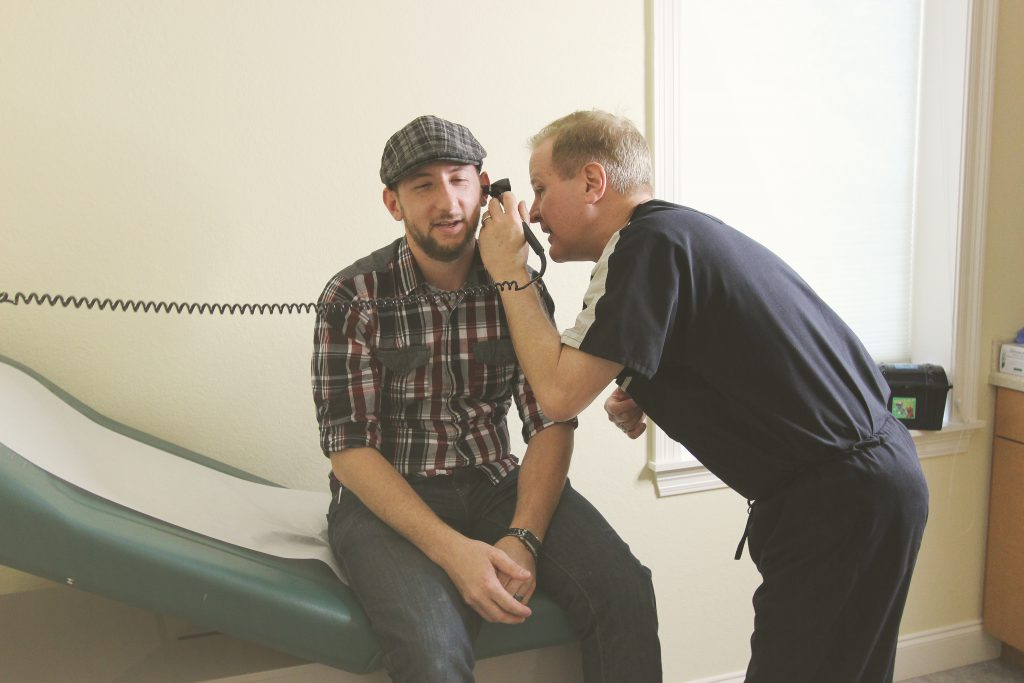 Dr. Riesberg examining the ear canal of a patient.