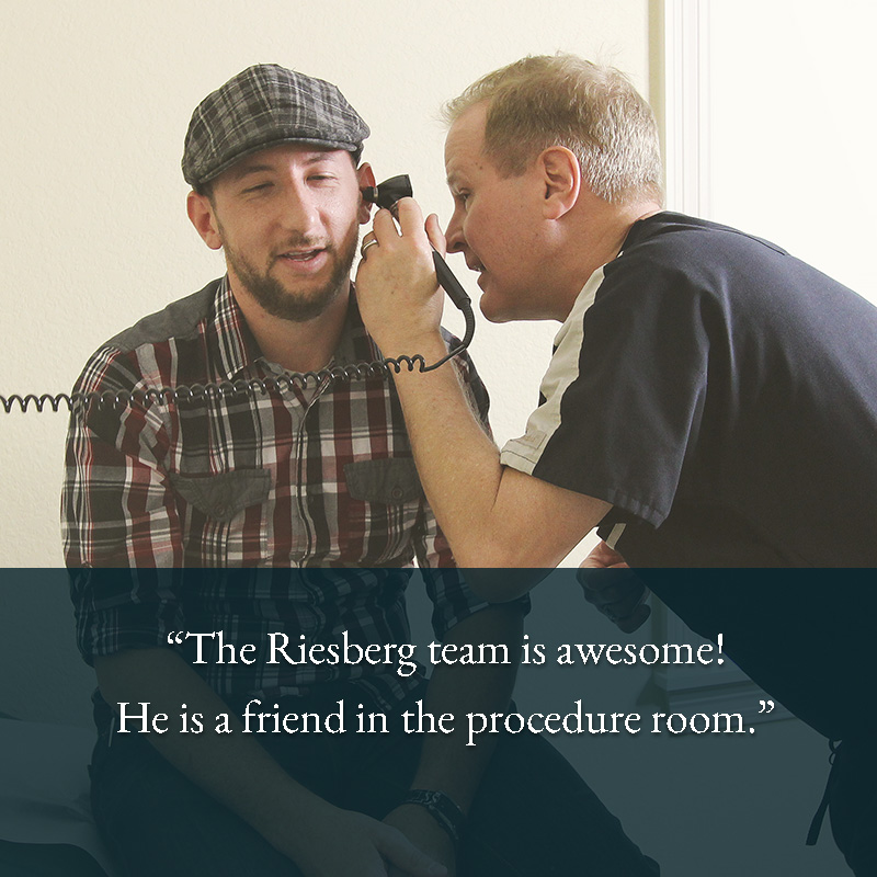 Dr. Riesberg using an otoscope to check the patient's ear canal.