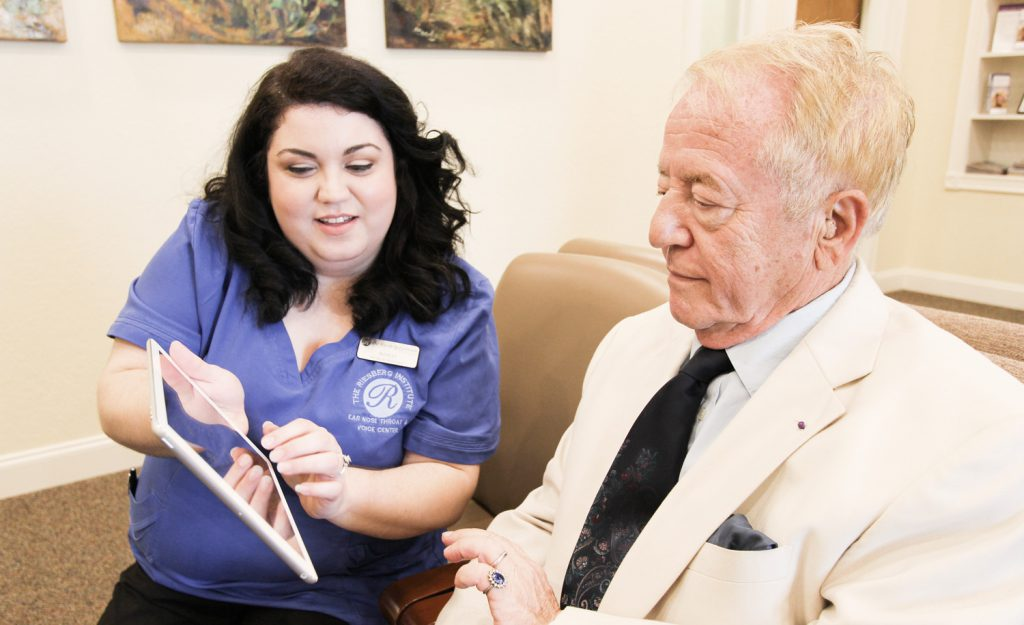 Office staff member assisting new patient with tablet use.