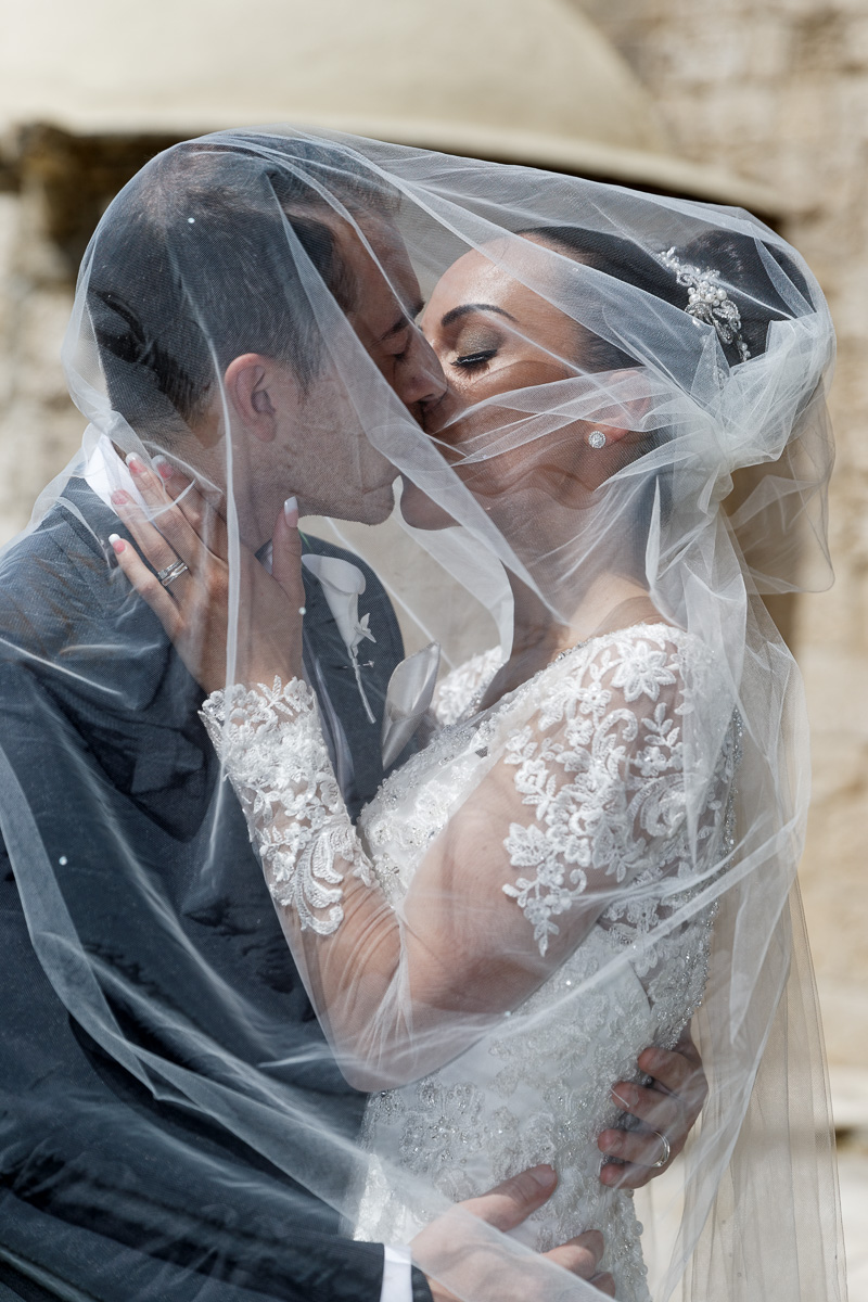 portrait of bride and groom covered in a white veil