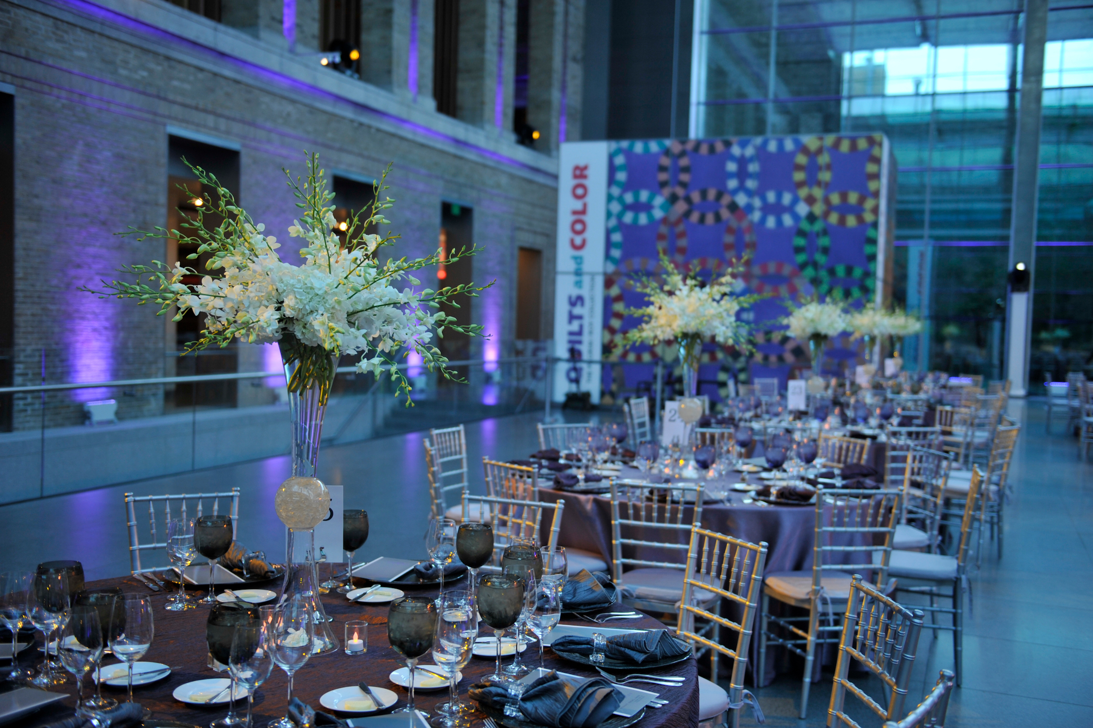 White floral centerpieces on purple tables with silver chairs in a vaulted, glass and stone room.