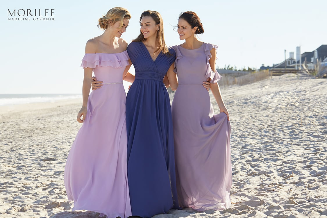 Three bridesmaids walking on a beach
