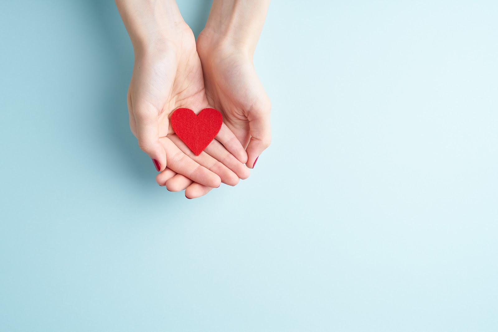 Virtual fundraiser: Pair of hands holding a cutout heart