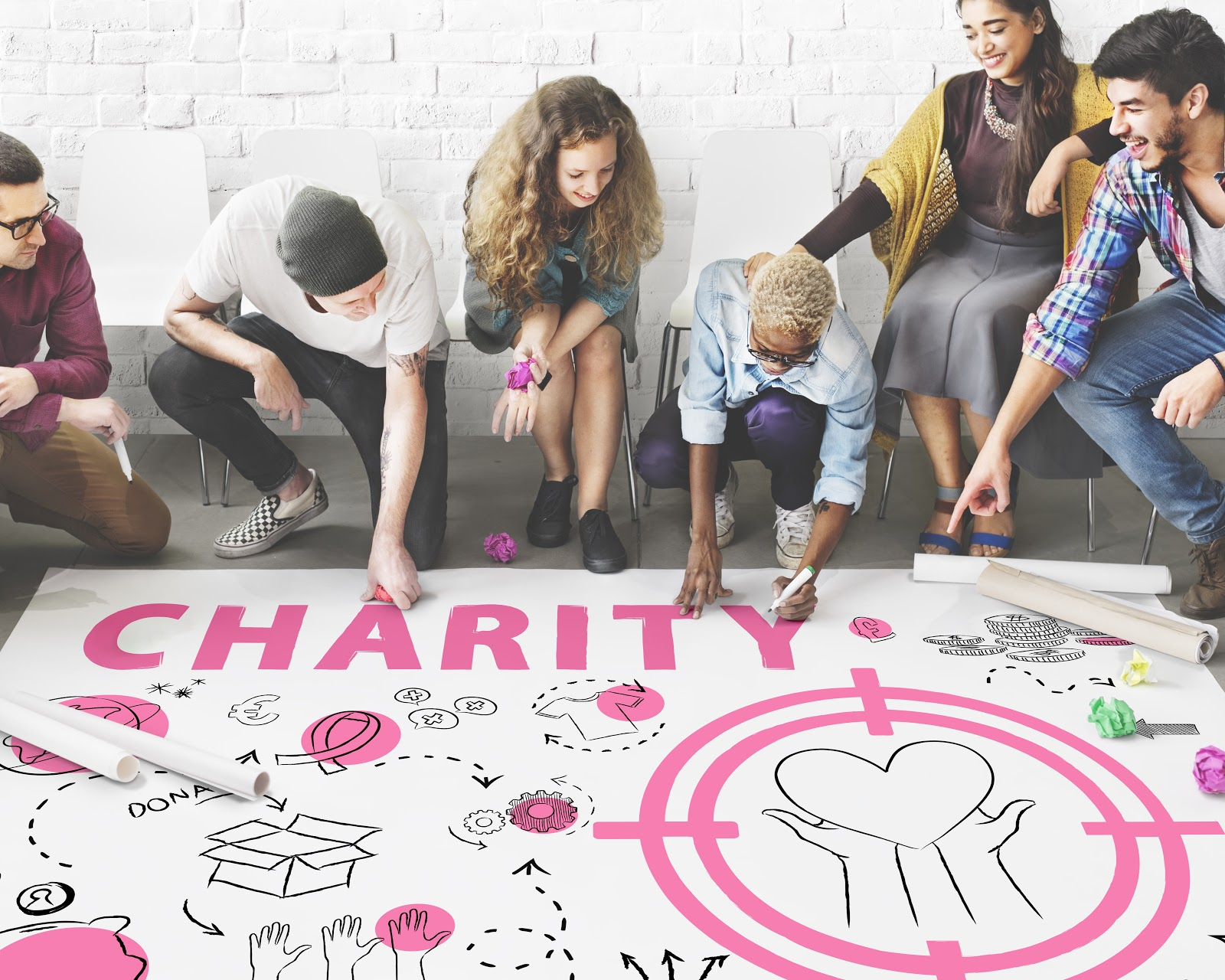 "Virtual fundraising events: Group of people drawing on large poster that reads ""Charity"""