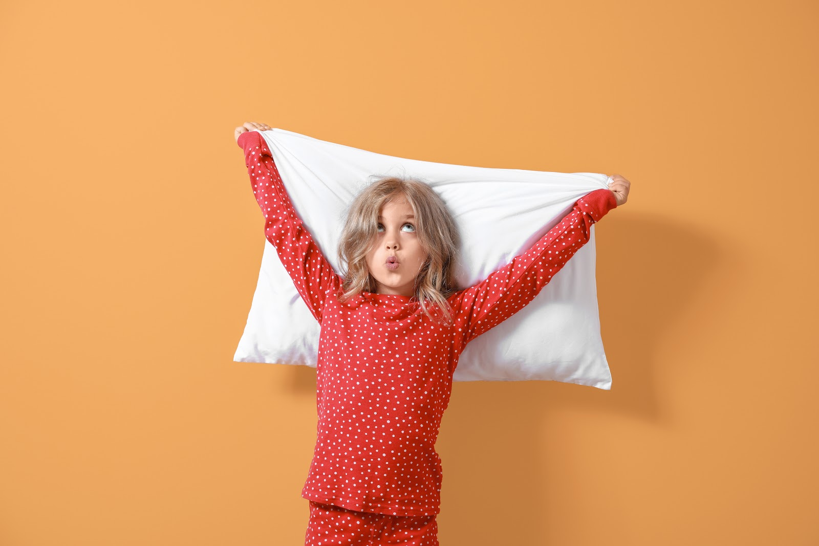 School fundraising ideas: Little girl in pajamas holding pillow up