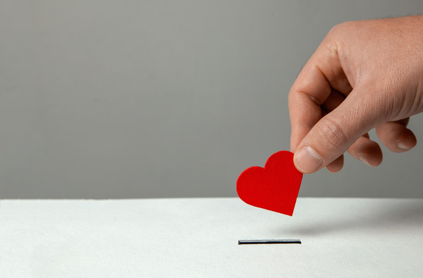 Man dropping a red heart inside box