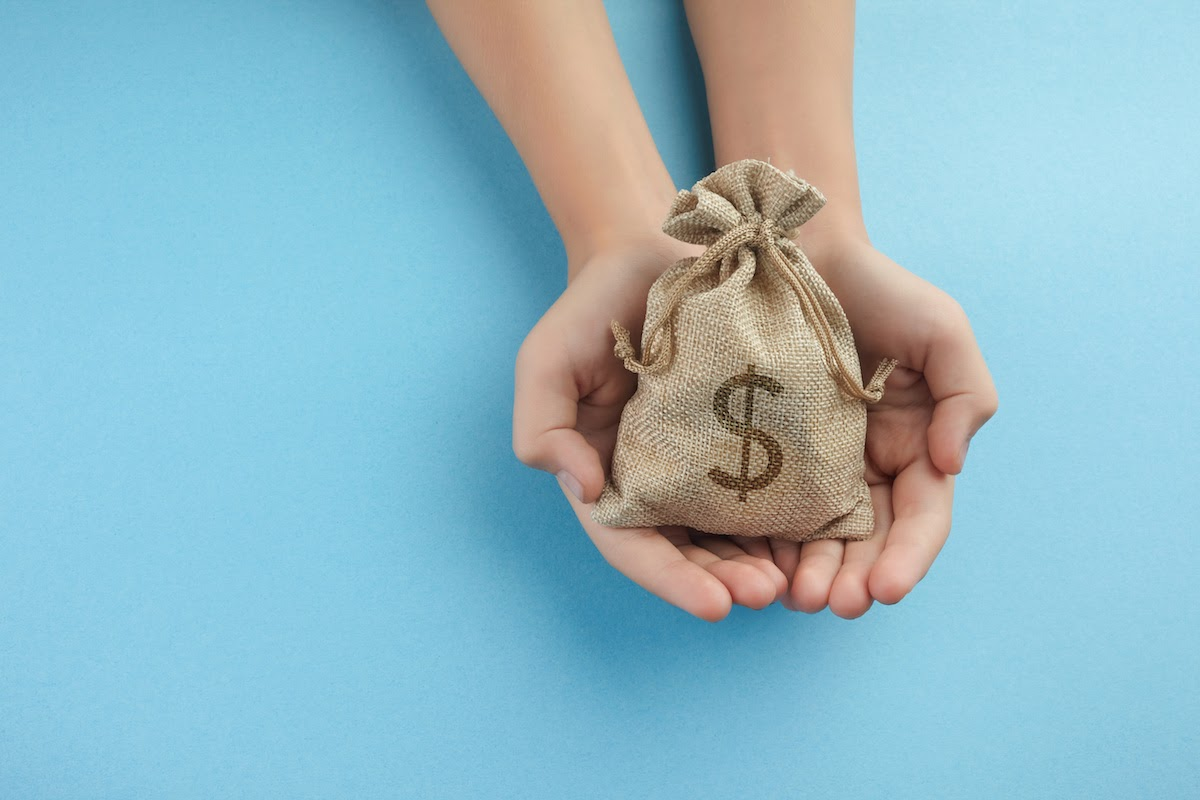 planned giving: hands holding a bag of money