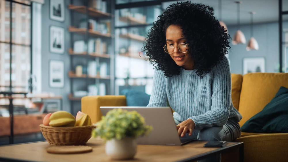 donor database: Woman sitting on a couch while using her laptop