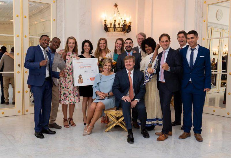 een groep mensen met het koninklijk paar op de foto