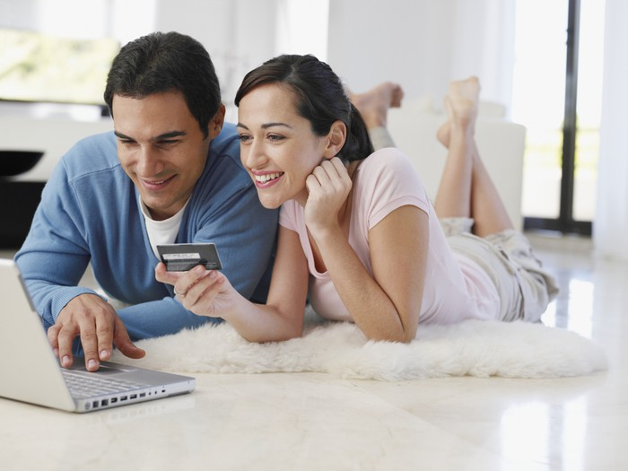 people smiling and holding a credit card