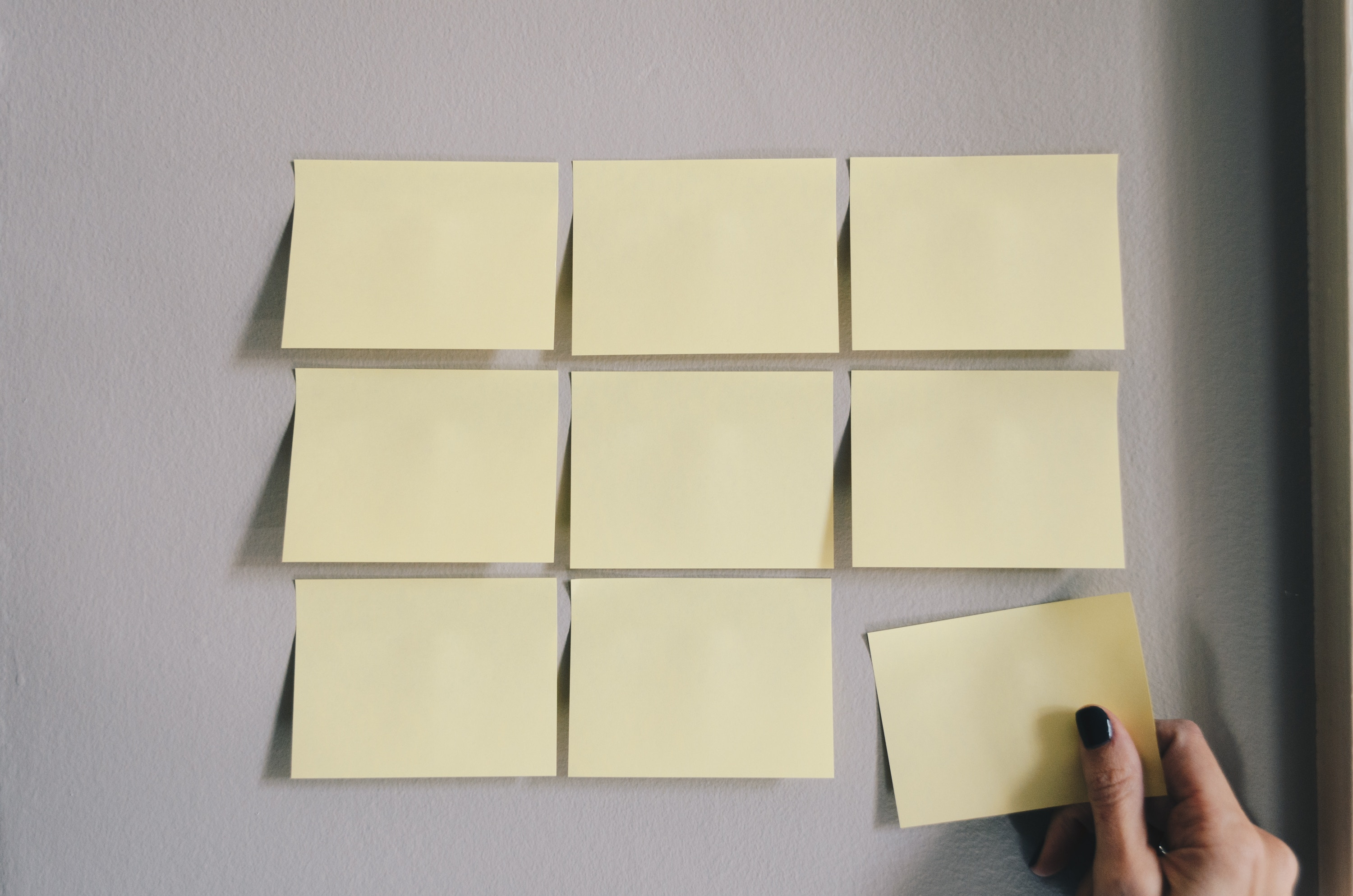 Blank sticky notes on a wall.