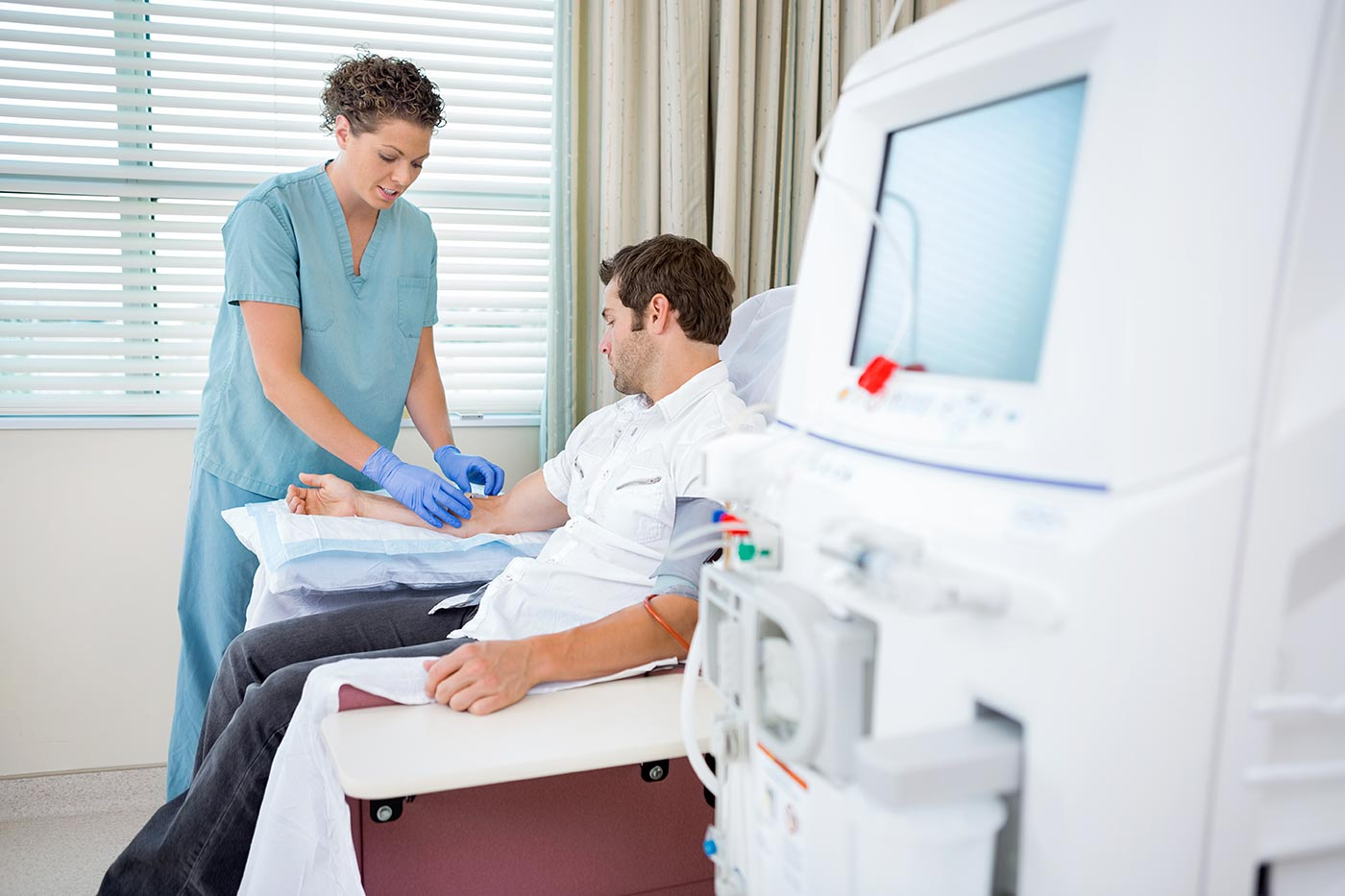 Image of man receiving dialysis from woman nurse.