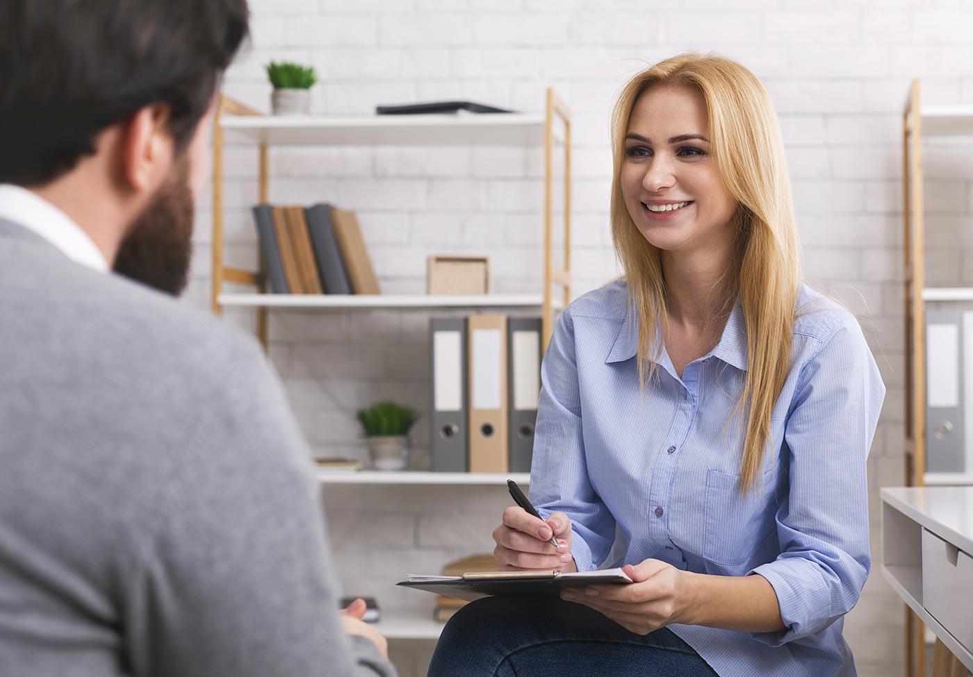 Woman interviews man.
