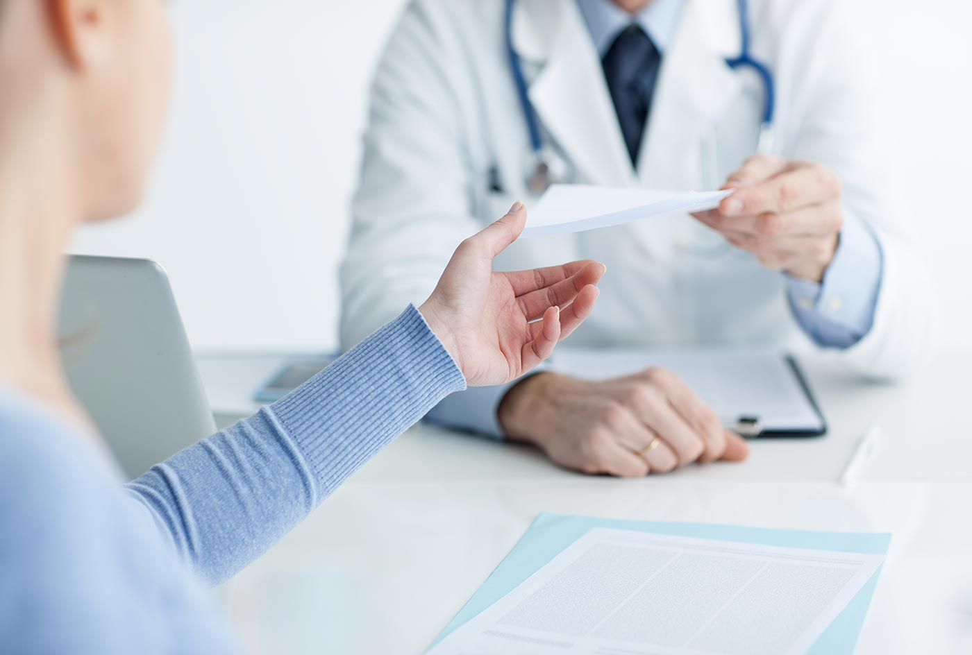 Image of physician handing woman a prescription.
