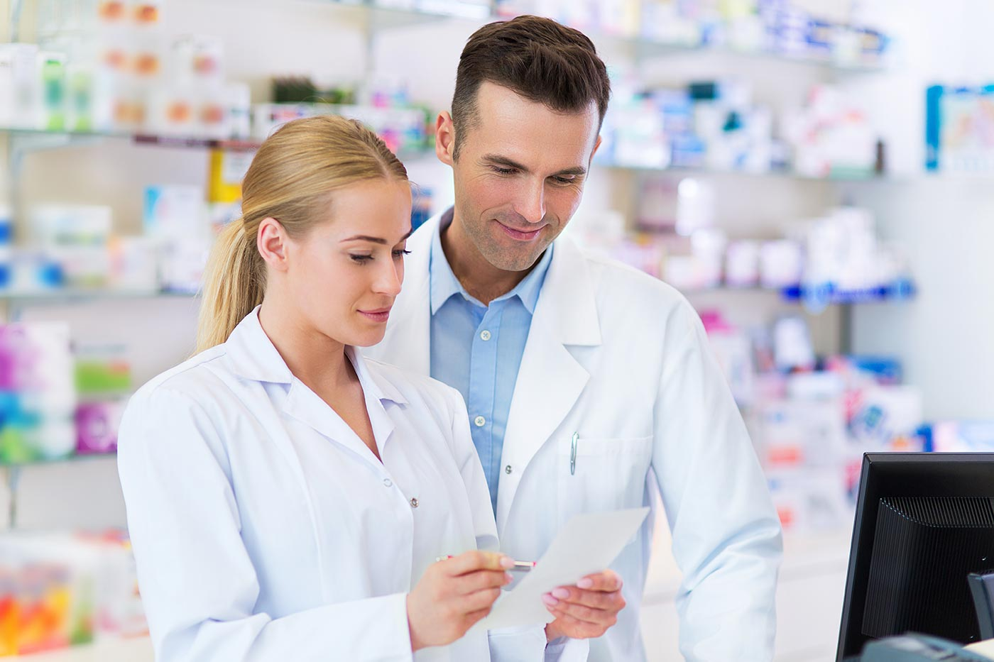 Man and woman in lab coats review piece of paper.