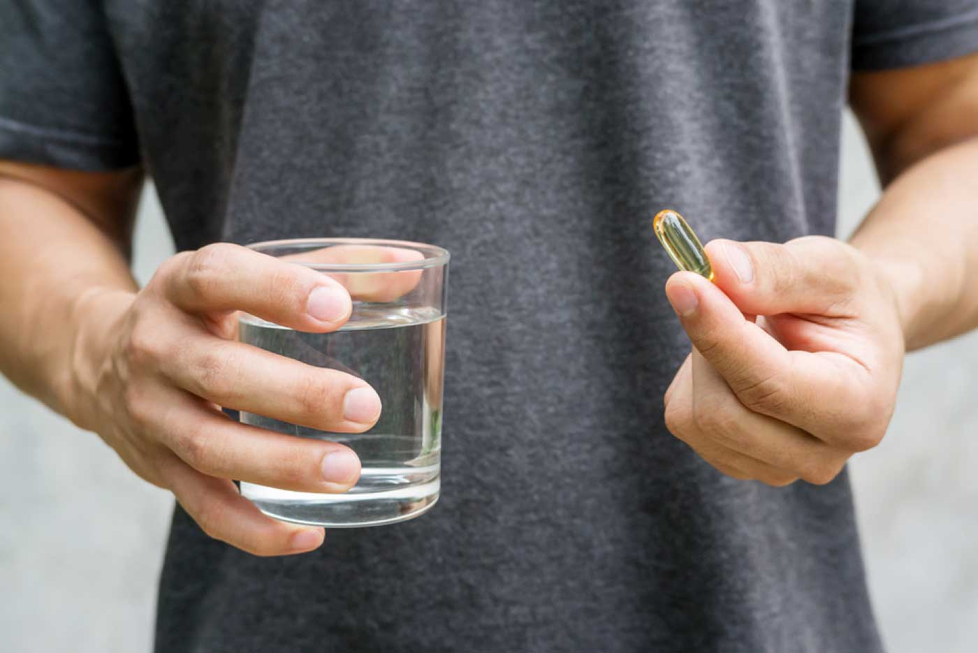 Person holding glass of water and vitamin.