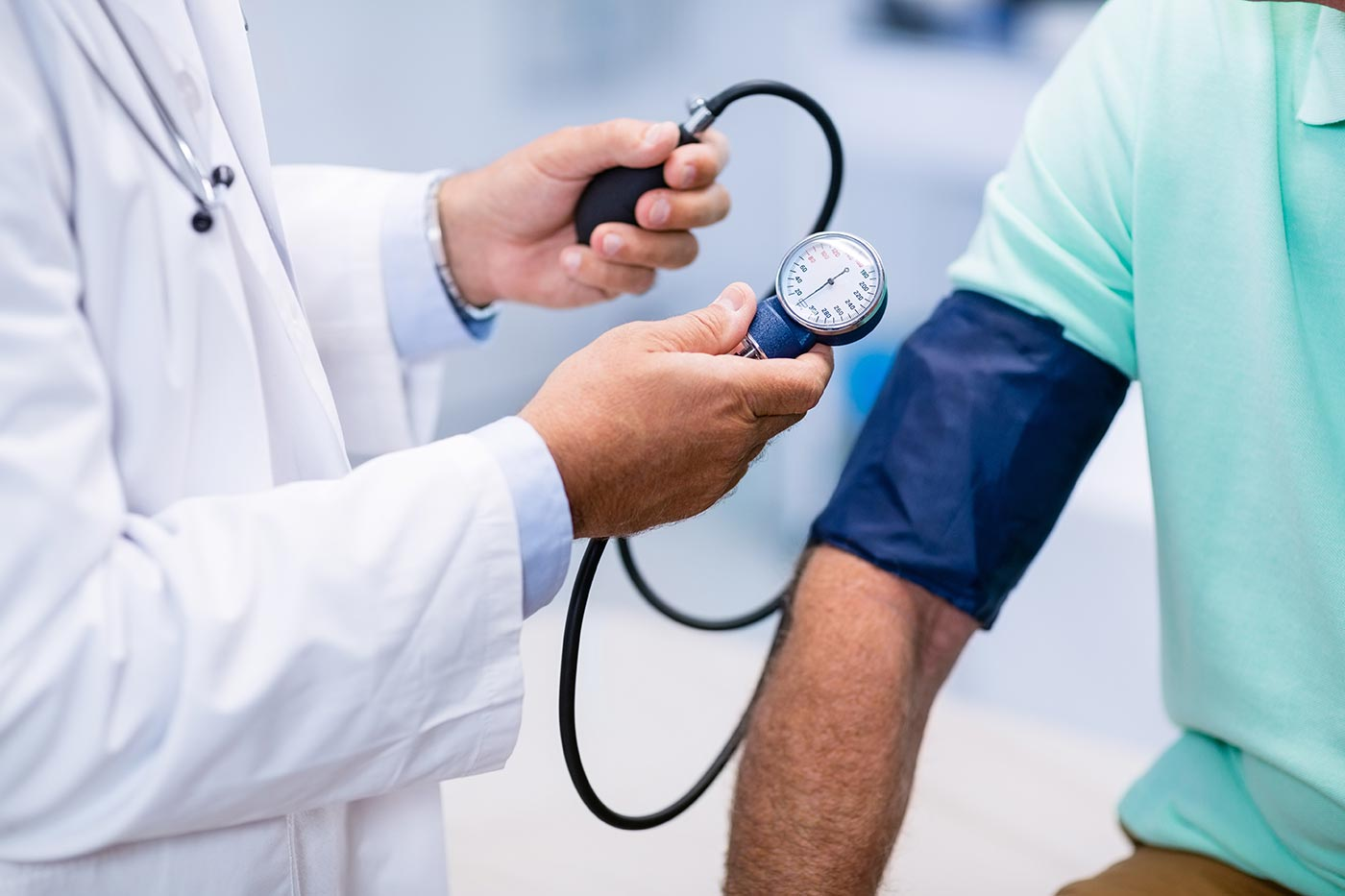 Physician takes a person's blood pressure.