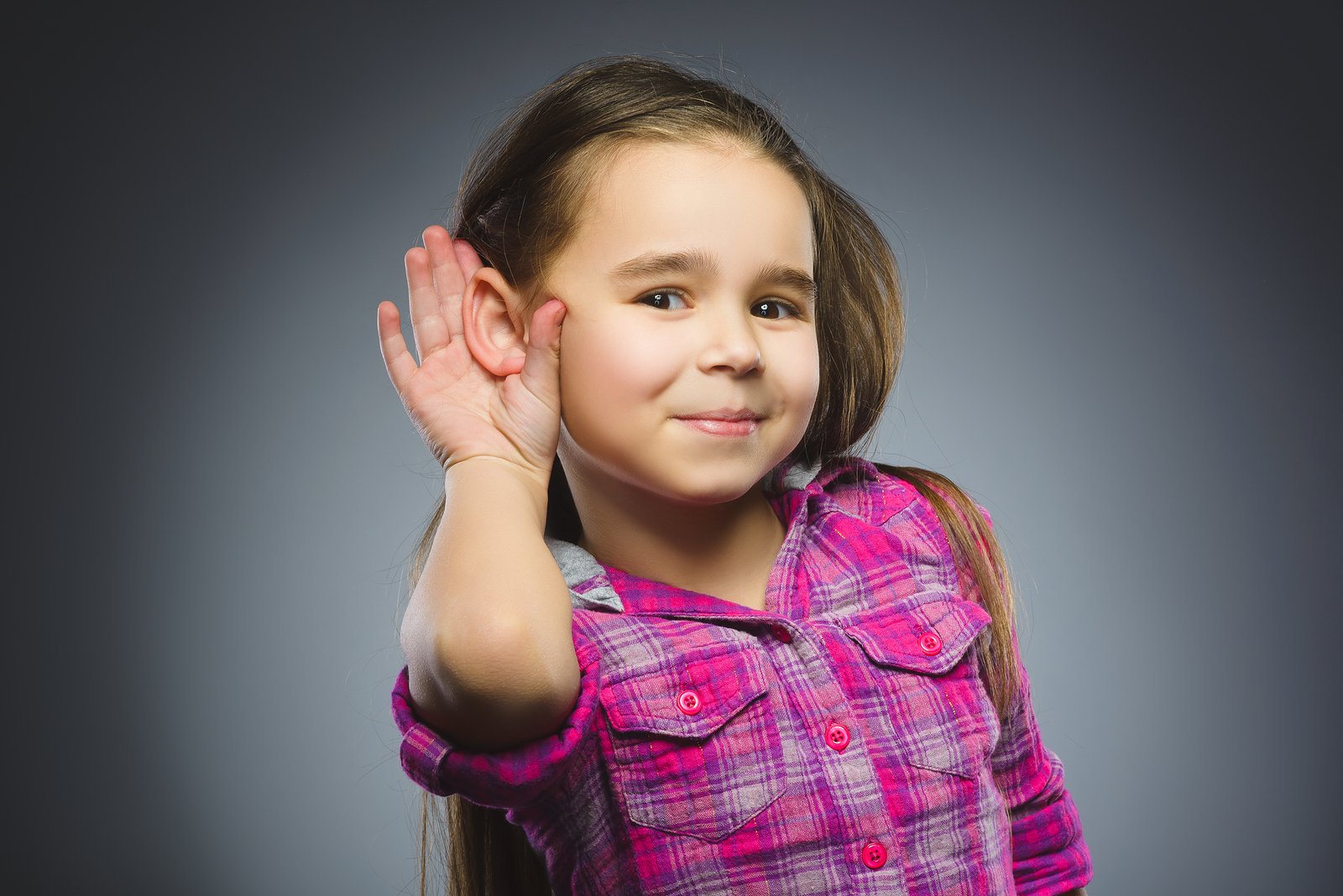 LIttle girl cupping her hand behind her ear to hear better.