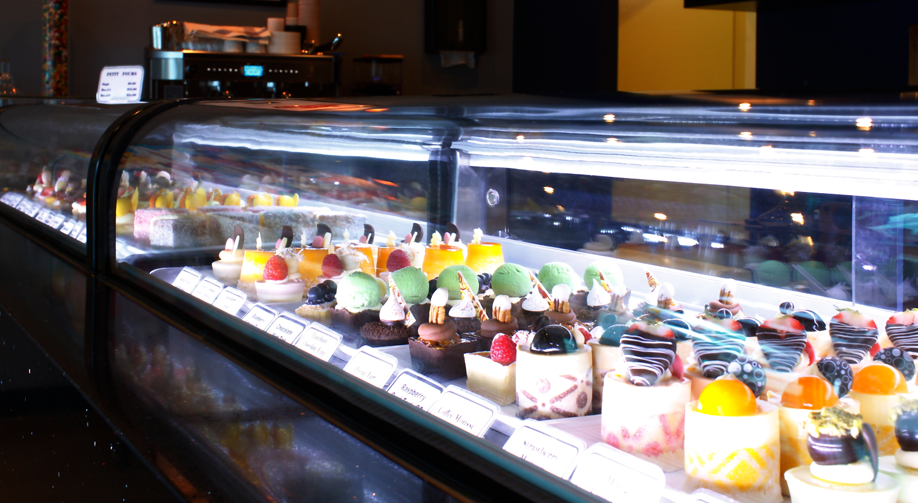 open glass refridgeration cabinet with desserts on display