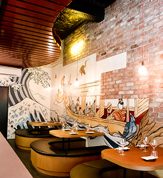 japanese style interior space, with rounded booths, brick walls, and painted mural