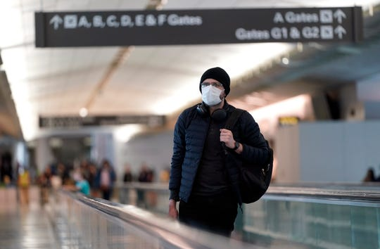 An airline passenger wearing a mask makes his way through the International Terminal at San Francisco International Airport Saturday, March 7, 2020, in San Francisco. As cases of the coronavirus surge in Italy, Iran, South Korea, the U.S. and elsewhere, many scientists say it's plain that the world is in the grips of a pandemic — a serious global outbreak.