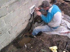 Man wiring electrics stood in a puddle