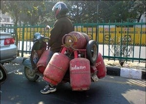 Man riding a scooter with gas canisters hanging from the sides