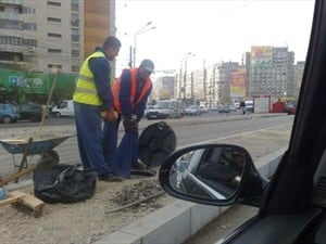 Workers holding another worker by the trousers down a manhole