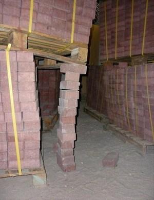 Bricks propping up a pallet of bricks