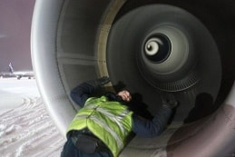 Man posing inside an aircraft engine