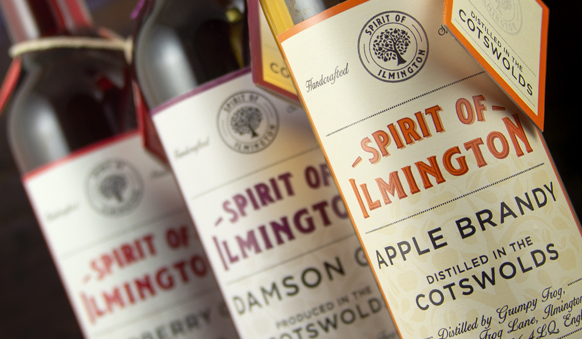 An image of brandy and gin label designs by Pemberton & Whitefoord LLP. The range includes Apple Brandy and gin and features a unique logo design and swing tags on the bottle necks. The bottle redesign is for the Spirit of Ilmington.